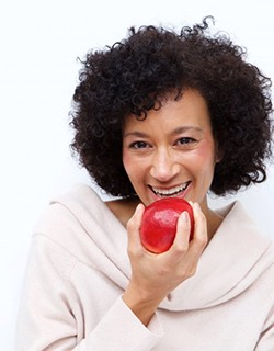 older woman eating red apple
