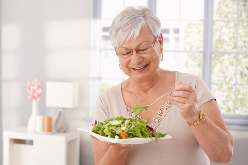 an older woman preparing to eat a salad while wearing dental implants