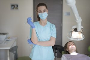 Hygienist at dentist wearing a face mask.
